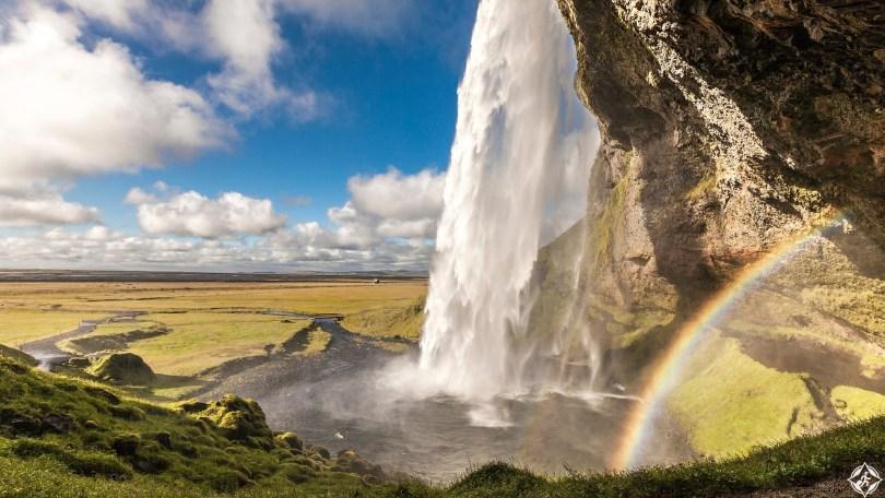 Water cascading into pool creating rainbow at Seljalandsfoss.