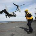 A Royal Navy airman stands on the flight deck of the amphibious assault ship USS Kearsarge (LHD 3) while an MV-22 Osprey takes off. US Navy Photo