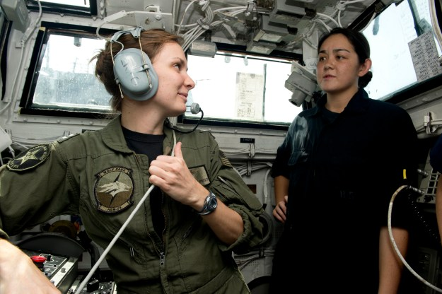 Lt. Brittny Lambert talks to a midshipman about flight operations in the landing signal officer shack aboard the guided-missile destroyer USS William P. Lawrence (DDG-110). US Navy Photo