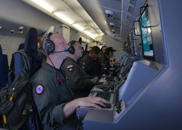 Crew members on board a P-8A Poseidon assigned to Patrol Squadron (VP) 16 man their workstations while assisting in search and rescue operations for Malaysia Airlines flight MH370 on March, 16 2014. US Navy Photo