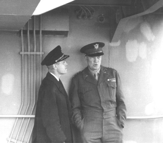 "Naval Reserve Captain Edmond J. Moran receives urgent and specific instructions from Supreme Allied Commander Europe General Dwight D. Eisenhower on board the destroyer USS Thompson after D-Day. The general ordered Moran back to the United States ""for more supplies and equipment to keep the invasion going."""