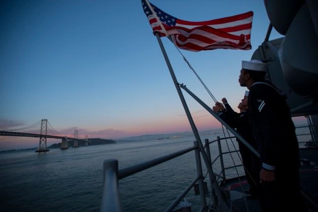 ailors assigned to the future amphibious assault ship USS America (LHA 6) perform evening colors on the ship's fantail while moored in San Francisco Bay. US Navy Photo