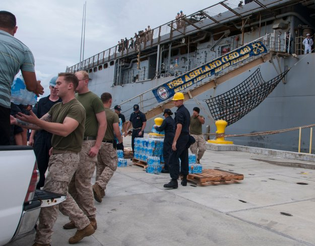Sailors and Marines load cases of water onto the amphibious dock landing ship USS Ashland (LSD 48) in preparation for the ship getting underway to deploy to Saipan on Aug. 6, 2015. US Navy Photo