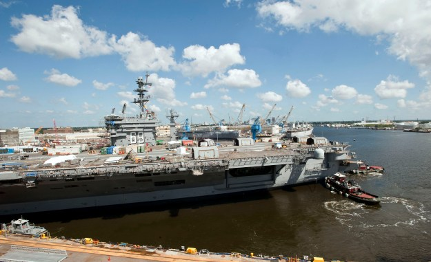 Tugboats guide the aircraft carrier USS Dwight D. Eisenhower (CVN 69) from her dry dock at Norfolk Naval Shipyard to a nearby pier following a scheduled dock flooding earlier in the morning of Aug. 26, 2014. US Navy photo.