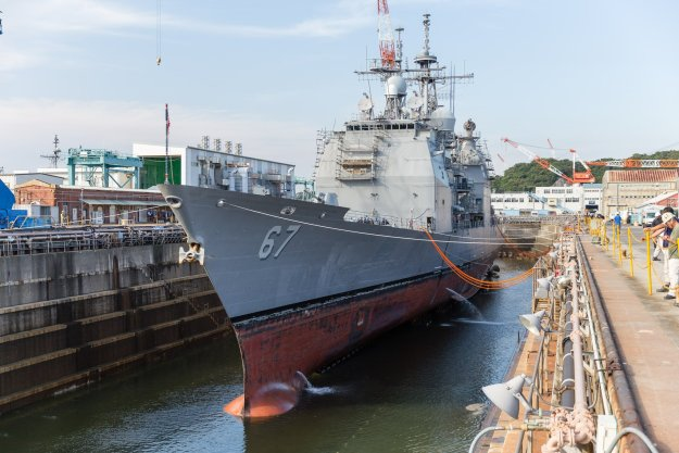 Water is drained from a dry dock at U.S. Naval Ship Repair Facility and Japan Regional Maintenance Center (SRF JRMC) Yokosuka preparing the Ticonderoga-class guided-missile cruiser USS Shiloh (CG 67) for a scheduled maintenance availability in July 2015. US Navy photo.