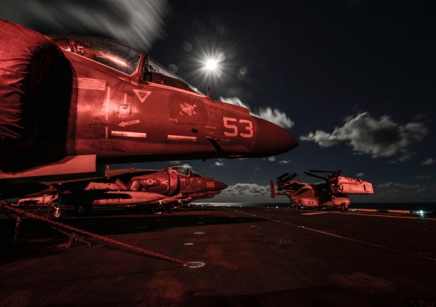 AV-8B Harriers and an MV-22 Osprey sit on the flight deck at night aboard the amphibious assault ship USS Bataan (LHD 5) on Oct. 8, 2014. US Navy photo.