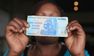 A woman holds a 100 trillion dollar note on the streets of Harare in this Friday, Oct. 28, 2016 photo. A single $100 trillion dollar note can fetch $5 in cash from street currency traders in this once prosperous Southern African nation where many are desperate for solid financial footing. Now out of circulation, this symbol of Zimbabwe's economic ruin is receiving a warmer embrace than a new local currency the government is introducing this week. (AP Photo/Tsvangirayi Mukwazhi)