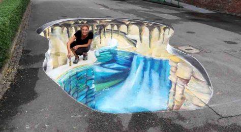 Eine Höhle tut sich auf dem Gelände der Zeche Zollern auf. Straßenmalerin Lydia Hitzfeld (im Bild) und ihre Tochter Vanessa haben das 3-D-Bild beim Unterwelten-Forum erschaffen. Foto: LWL / Hudemann