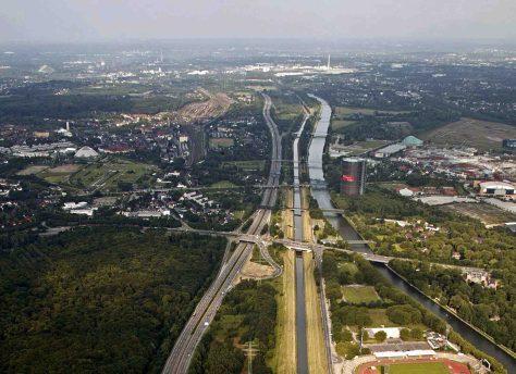 Das Ruhrgebiet gehört in Europa zu den dicht besiedeltsten Ballungsräumen und ist größter Verkehrsknotenpunkt. Das Luftbild zeigt die Emscher entlang der Autobahn 42. Foto: Emschergenossenschaft