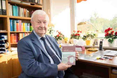 """Prof. Dr. Werner Besch, Emeritus von der Universität Bonn, mit seinem Buch """"Luther und die deutsche Sprache"""". (c) Foto: Volker Lannert/Uni Bonn"""