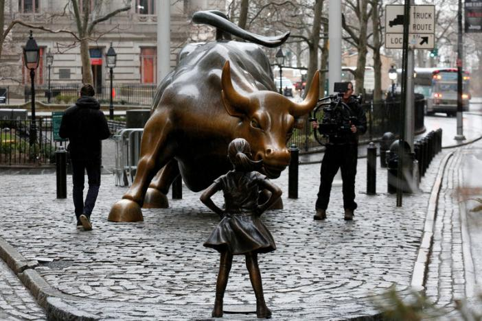 A camera man films a statue of a girl facing the Wall St. Bull, as part of a campaign by U.S. fund manager State Street to push companies to put women on their boards, in the financial district in New York, U.S., March 7, 2017. REUTERS/Brendan McDermid