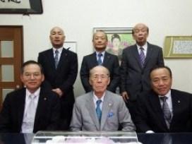 写真前列右から里永社長・石川会長・中野専務、後列右から真鍋取締役・山崎常務・藤井取締役
