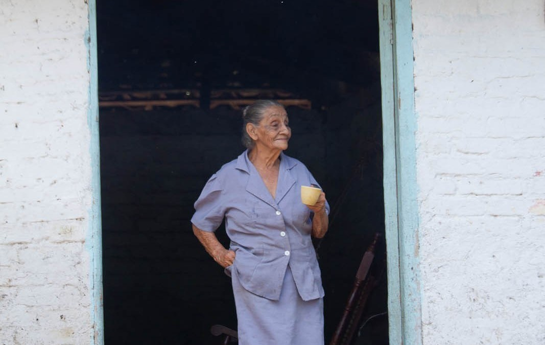 Elderly woman with cup of coffee in doorway to her home, Apatu, Terrabona, Matagalpa, Nicaragua