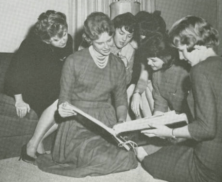 Black and white photo of group of young women looking through a book. They are seated or kneeling on the floor. Smiling and interested.