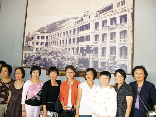 Some former Sacred Heart students stand in front of a photo of the school's old building, which had been demolished due to termites. (Photo by John Chan)