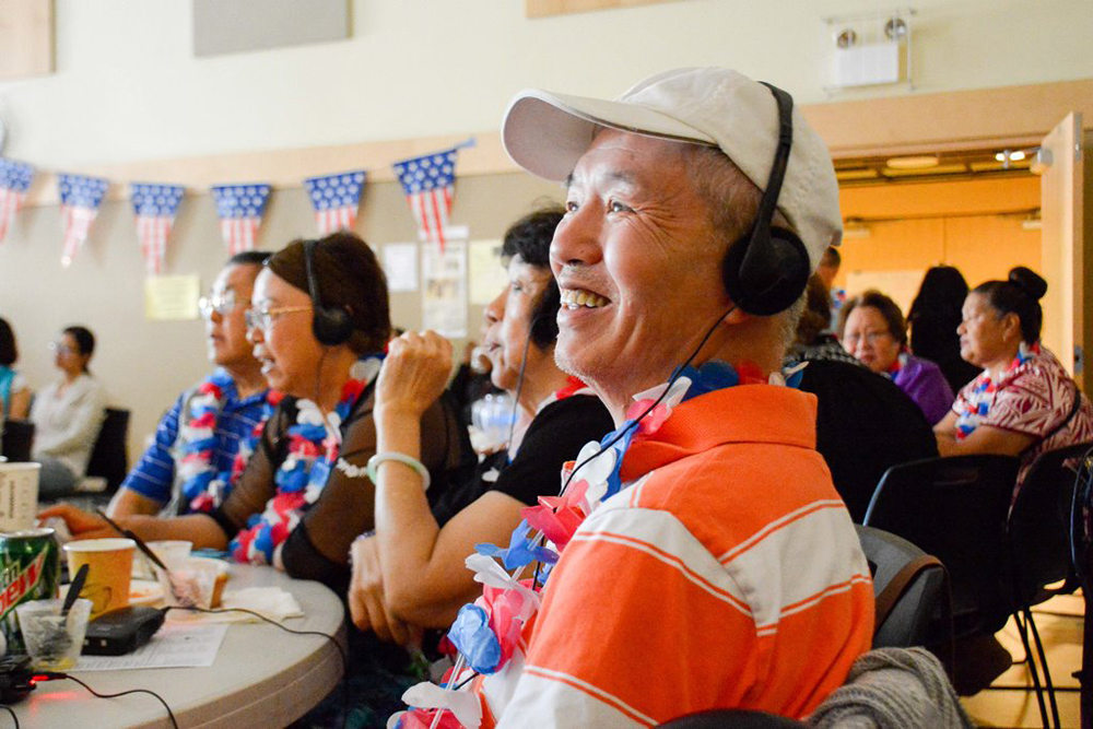 A participant at one of the Cantonese tables listens during a portion of the live cast of the Presidential Candidate Forum. (Photo provided by ACRS)