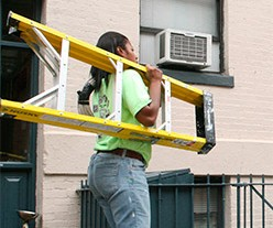 A worker carrying a ladder