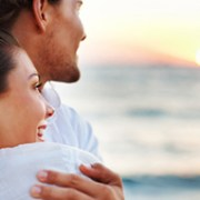 A wonderful sunset and a warm loving hug. What could possibly be better. Portrait of young couple looking at the sunset