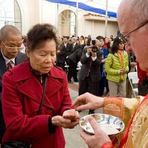 REV. KEVIN W. VANN, BISHOP OF ORANGE, OFFERS COMMUNION DURING A TET FESTIVAL CELEBRATION AT THE VIETNAMESE CATHOLIC CENTER IN SANTA ANA. COURTESY OC REGISTER