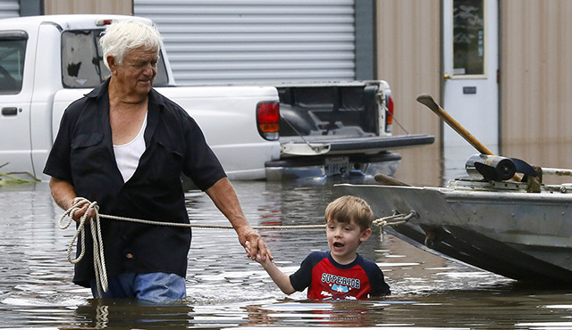 RICHARD ROSSI AND HIS 4-YEAR-OLD GREAT-GRANDSON JUSTICE WADE THROUGH WATER AUG. 15 AFTER THEIR HOME FLOODED IN ST. AMANT, LA. / PHOTO: CNS PHOTO/JONATHAN BACHMAN, REUTERS
