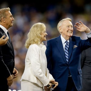 HALL OF FAME LOS ANGELES DODGERS BROADCASTER VIN SCULLY, FRONT RIGHT, AND WIFE SANDI, ACKNOWLEDGE THE FANS AS THEY ARE JOINED BY ACTOR KEVIN COSTNER, SECOND FROM LEFT, AND PITCHER CLAYTON KERSHAW, LEFT, DURING VIN SCULLY APPRECIATION DAY BEFORE THE TEAM'S BASEBALL GAME AGAINST THE COLORADO ROCKIES, FRIDAY, SEPT. 23, 2016, IN LOS ANGELES / PHOTO: AP PHOTO/JAE C. HONG