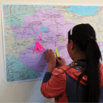 9th grade student highlighting her village on a map during the KMEECS round table meeting in 2015.