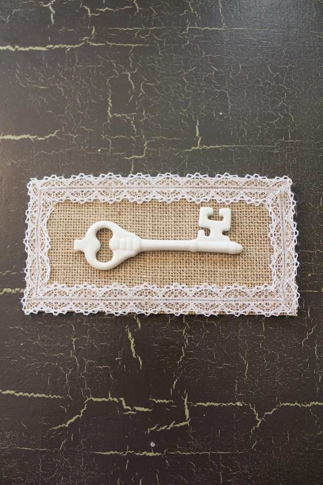 Key Artwork   A white porcelain key, burlap backing and lace all come together in this vintage-inspired mounted key artwork. A super easy DIY for a super cute decor item!