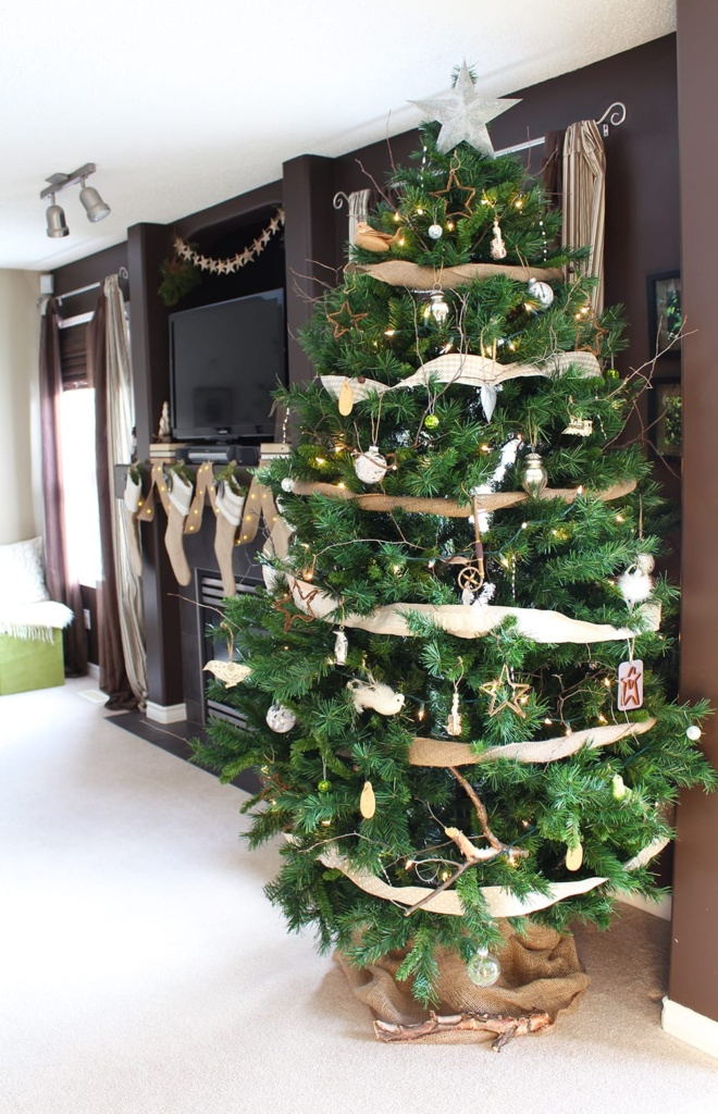 Nature inspired holiday decor featuring a faux Christmas tree decked out with real branches, burlap stockings and plenty of bird ornaments, stars and fresh greenery.