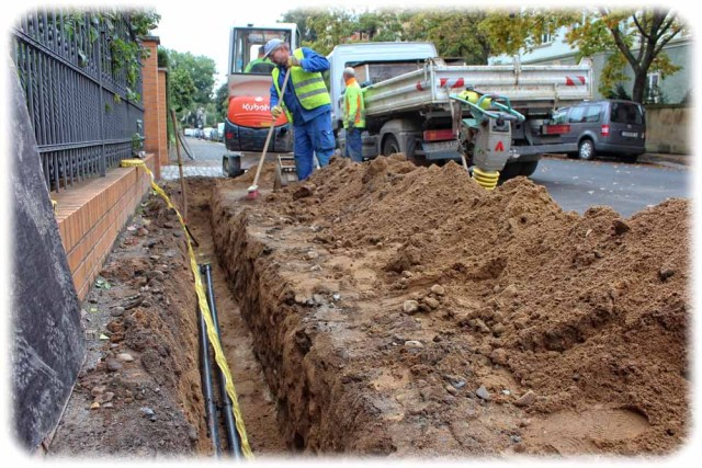 Teilweise baggern die Arbeiter schmale Gräben in die Fußwege, um die Glasfasern zu verlegen. Wo es aber geht, verwenden sie das Baum-schonende Bohrspülverfahren. Dabei graben sie nur Löcher und bohren die Rohrunnel dann unterirdisch mit Spezialbohrern. Foto: Heiko Weckbrodt