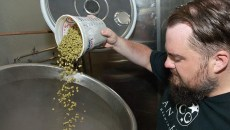Anthony pours hops into a brewing vat (Mark Hancock)