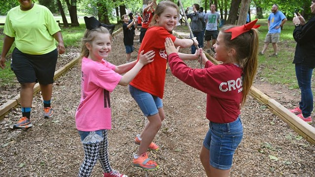 Girls from Crossings Christian School have fun while walking a tight wire with aid from hanging ropes, at Camp Dakani.  mh