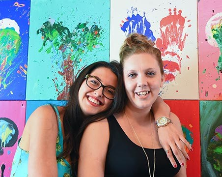 Left to right, Lindsey Michelle Webb and Kelly Brinkmeyer with breast-print paintings, 9-22-15.  (Mark Hancock)