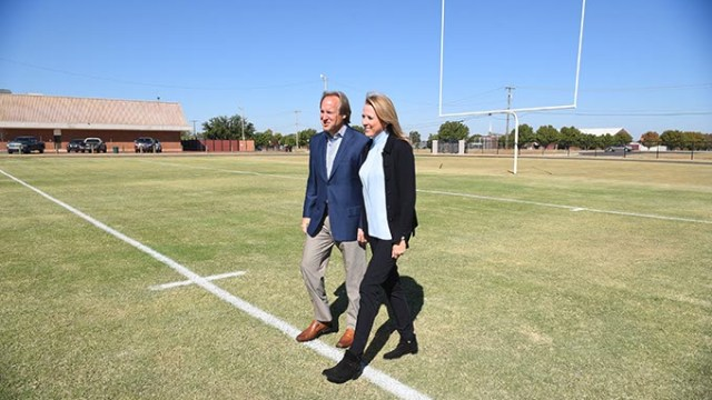 Tim and Liz McLaughlin helped start the Fields and Futures Foundation, shown walking a new football field constructed at Webster Middle School, 10-14-15.  (Mark Hancock)