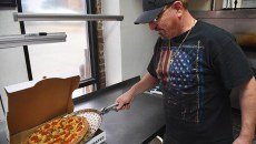 Frank Sweiss, owner of All American Pizza with eight metro locations, takes a fresh baked pepperoni and mushroom pizza out of the oven and into a box, at the 16726 N. Pennsylvania location, 12-8-15.  (Mark Hancock)