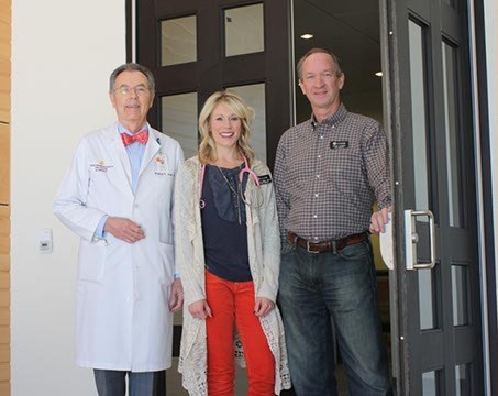 Volunteer Dr. Richard V. Smith, physician assistant Lindsay Seal and Steve Turner, director, stand at the entrance of Crossing Community Clinic in The Village. The clinic provides healthcare options for the uninsured.  (Laura Eastes)