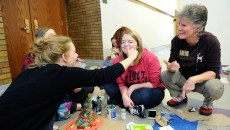 Lena Koehler puts frosting on Natalie Trujillo's face as Nancy Boudreau looks on at Classen SAS in Oklahoma City, Wednesday, Dec. 9, 2015.  (Garett Fisbeck)