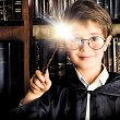 A boy stands with magic wand in the library by the bookshelves with many old books. Fairy tales. Vintage style.