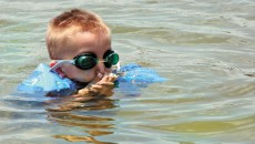 young boy plugs his nose while learning to swim