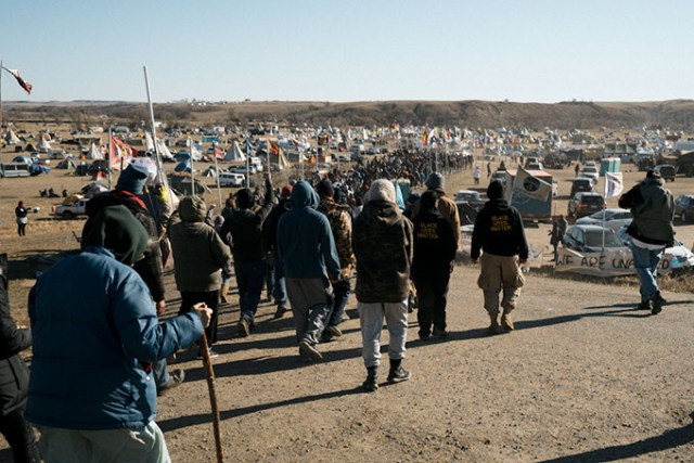 Hundreds of campers at North Dakota's Standing Rock Indian Reservation participate in a prayer ceremony. Indigenous tribes from across North America show solidarity with Standing Rock Sioux Tribe's struggle to protect its natural resources and sacred land. (Wade Dunstan / for Oklahoma Gazette)