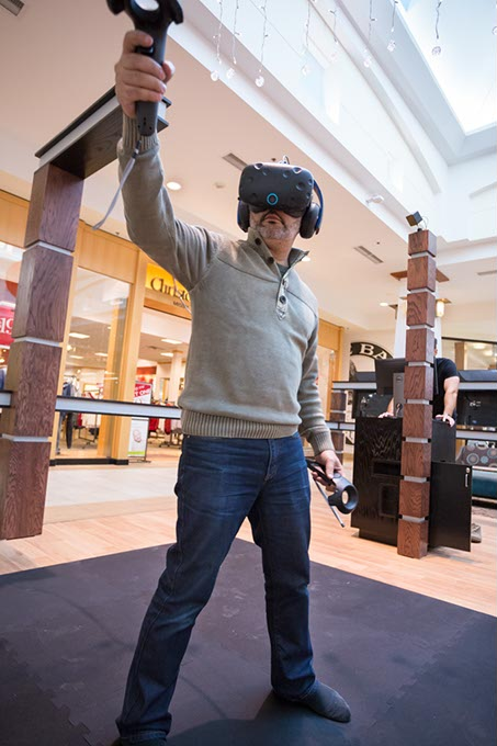 Tarek Dina, co-owner of Immersion House, demonstrates a virtual reality game. (Emmy Verdin for Gazette)