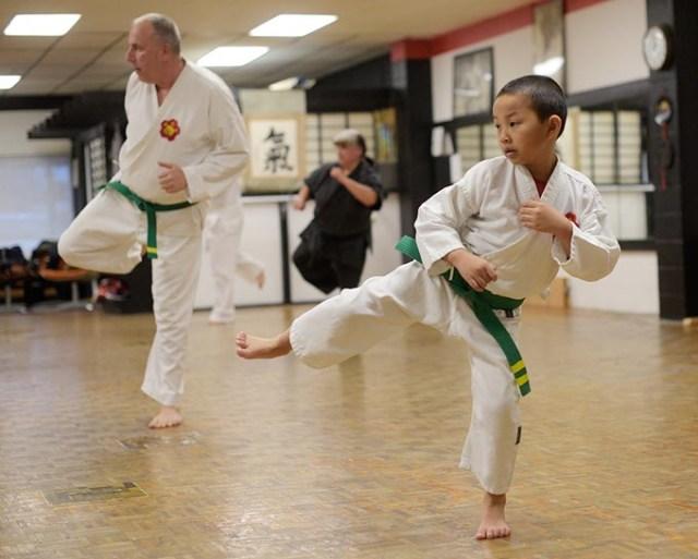 Ethan Nguyen, 7, and Robert Walker, 60, participate in a karate class at Okinawa Karate School. (Garett Fisbeck)