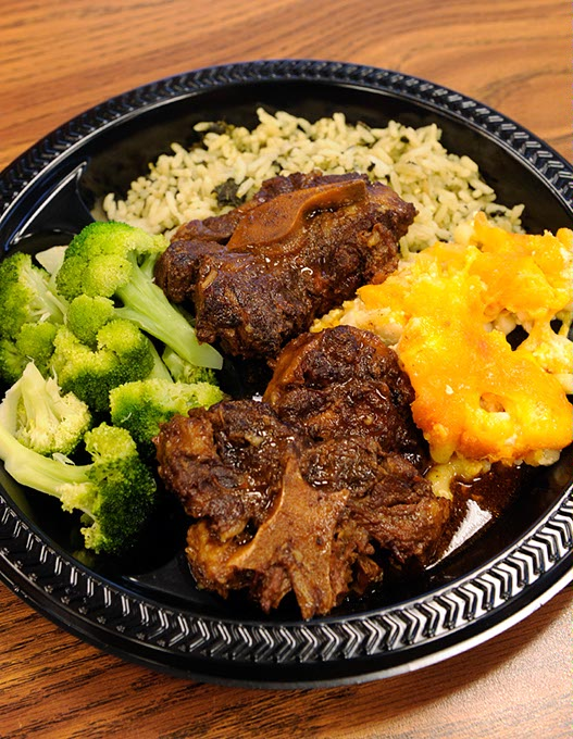 Oxtail, spinach rice, broccoli and macaroni and cheese at Carican Flavors in Oklahoma City. (Garett Fisbeck / file)