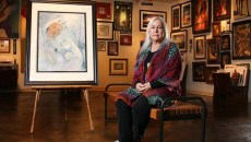 Connie Seabourn poses at 50 Penn Place Gallery, Tuesday, May 16, 2017.  The painting shown will be featured in her new exhibit, The Feminine Face of God, held at Oklahoma City University's Hulsey Gallery. (Cara Johnson)