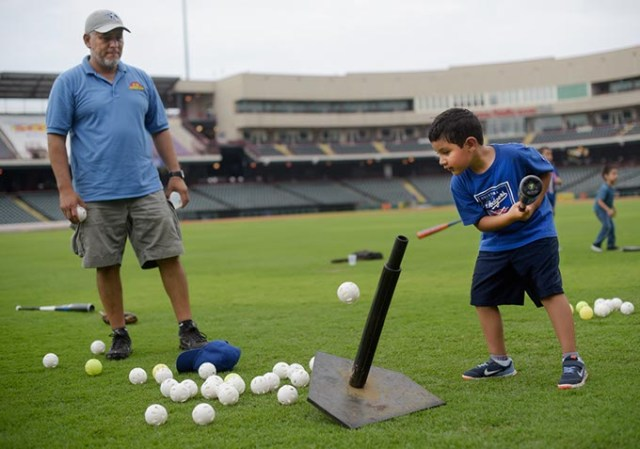 Emiliano Hernandez, 6, hits a ball off a tee as his father, Jorge, looks on during an OKC Dodgers Clinic in conjunction with Supermercados Morelos, Friday, July 28, 2017.  (Garett Fisbeck)