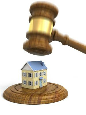 A gavel coming down on a house. Very high resolution 3D render.