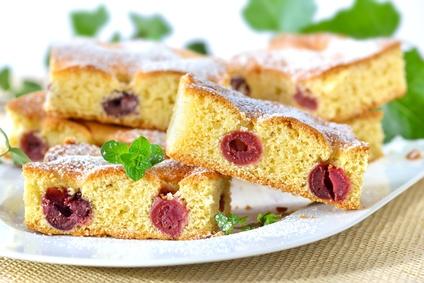 Geschnittener Kirschkuchen ( Blechkuchen mit Sauerkirschen ) mit  Puderzucker und Minzeblatt auf weier Porzellanplatte serviert -  Sheet cherry cake with powdered sugar and mint leaves