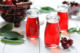 Cherry juice in jars and fresh ripe cherries on wooden background