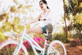 Woman on Bicycle with Legs Outstretched --- Image by © Royalty-Free/Corbis