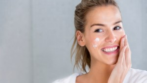 Beauty portrait of a woman using moisturizing cream