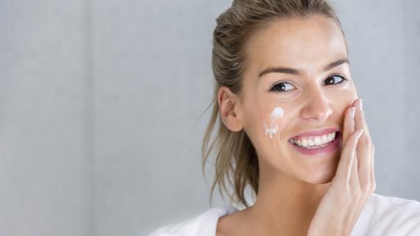 Beauty portrait of a woman using moisturizing cream